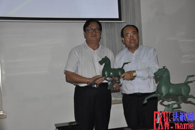 武威市委书记火荣贵(左一)向赵永亮赠送纪念品